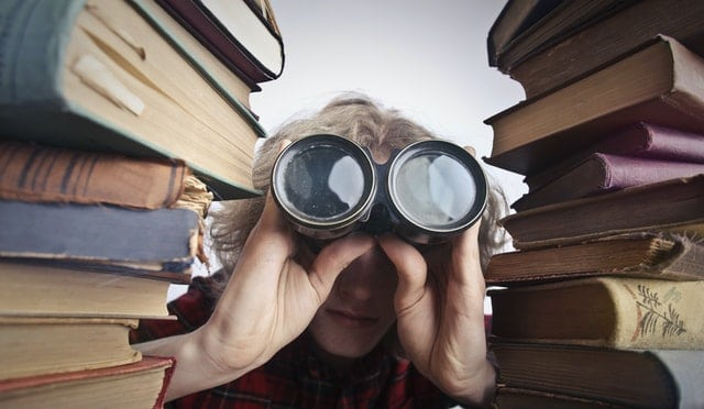 persona con prismaticos rodeada de libros