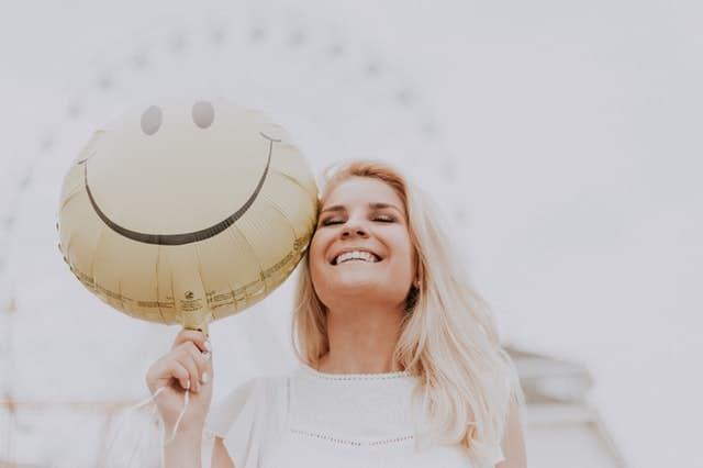 mujer feliz con globo sonriendo
