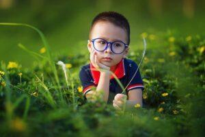 niño tumbado en un campo con flores