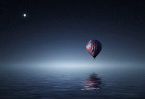 globo flotando en un mar calmado con la luna de fondo