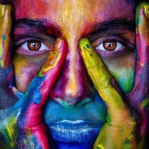 psicología del color mujer con la cara pintada de muchos colores