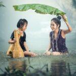 resiliencia madre tapa con una hoja a su hija bajo la lluvia