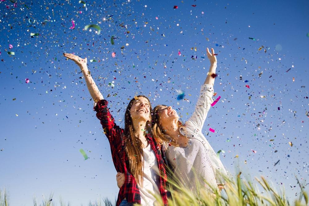 chicas llenas de felicidad en una lluvia de confetis